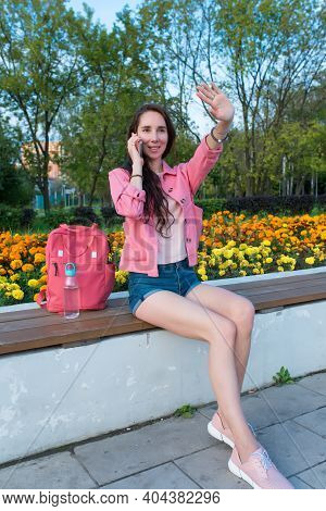 Woman In Summer In A City Park Waves Her Hand, Happy Smiles Rejoices, Meeting And A Date, Calling By