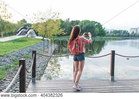 Woman In Summer In A City Park Near A Reservoir, A Pond, River And Lake, Records Video Photos On A S