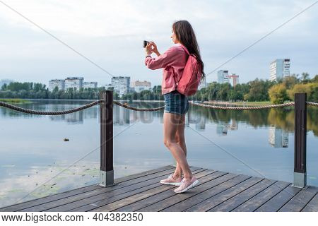 Girl In Summer In A City Park Near Reservoir, Pond, River And Lake, Records Video Photos On Smartpho