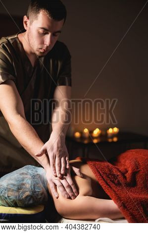 Male Masseur Doing Back Massage To Client Woman In Dark Room Of Massage Spa