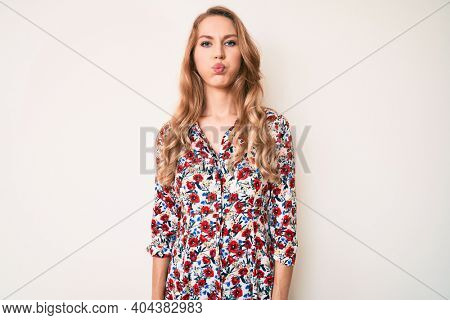 Young caucasian woman with blond hair wearing summer dress puffing cheeks with funny face. mouth inflated with air, crazy expression.