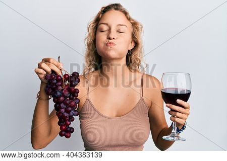 Beautiful caucasian woman holding branch of fresh grapes and red wine puffing cheeks with funny face. mouth inflated with air, catching air.