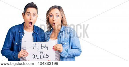 Couple of women holding my body my rules banner scared and amazed with open mouth for surprise, disbelief face