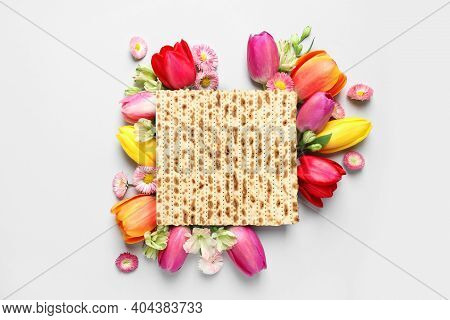 Tasty Matzo And Flowers On Light Background, Flat Lay. Passover (pesach) Celebration