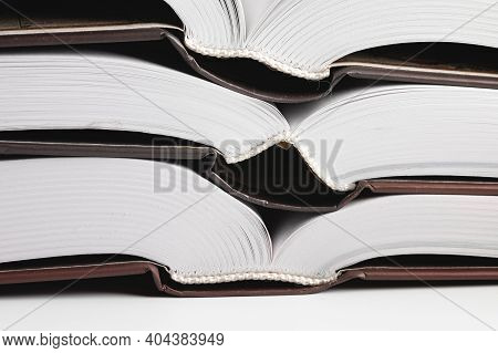 Close-up Of The Hardback Of A Thick Book On A Gray Background. Reading And Libraries