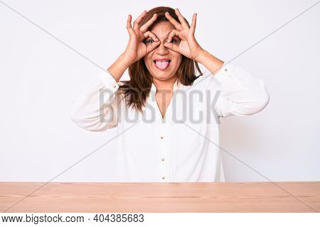 Middle age brunette hispanic business woman wearing casual white shirt sitting on the table doing ok gesture like binoculars sticking tongue out, eyes looking through fingers. crazy expression.