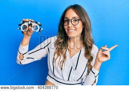 Young brunette woman holding optometry glasses smiling happy pointing with hand and finger to the side