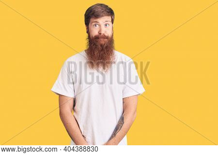 Handsome young red head man with long beard wearing casual white tshirt puffing cheeks with funny face. mouth inflated with air, crazy expression.