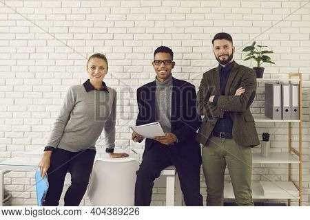 Team Of Three Happy Confident Young Business People Looking At Camera And Smiling