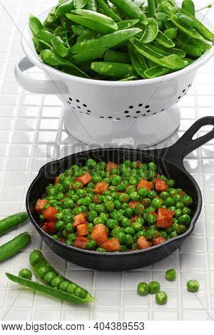 fresh green peas with ham in skillet and full of husk in colander