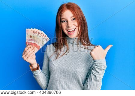Young red head girl holding 10 colombian pesos banknotes pointing thumb up to the side smiling happy with open mouth
