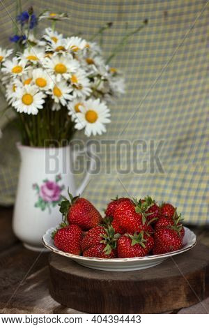 Chamomile And Cornflowers In A White Vintage Vase With A Rose, Strawberries In The Background. Summe