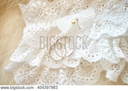 Wedding Rings Lie On The Bride's Lace Garter Against The Background Of White Fluff. Close-up, Macro