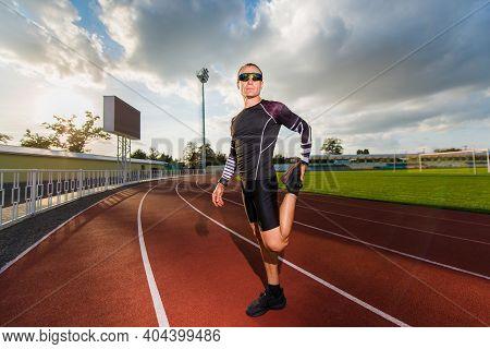 Runner Stretching His Legs In The Stadium