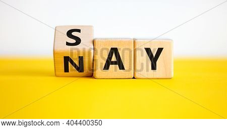 Say Nay Symbol. Turned A Cube, Changed The Word 'say' To 'nay'. Beautiful Yellow Table, White Backgr