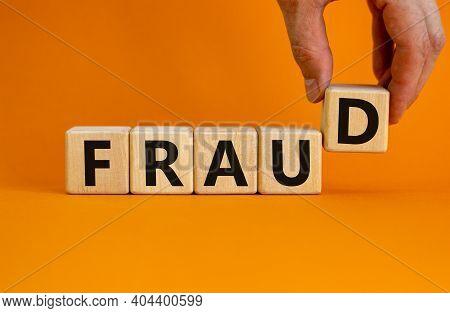 Fraud Symbol. Concept Word Fraud On Wooden Cubes On A Beautiful Orange Table. Businessman Hand. Oran