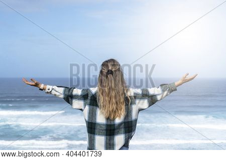 Beautiful Girl Looking At The Sea And Ocean Waves On Top Of The Beach Showing Happiness And Joy Seek
