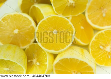 Fresh Ripe Lemons. A Background Of A Large Number Of Lemons, Cut In Half, Without Zest, Lying On The