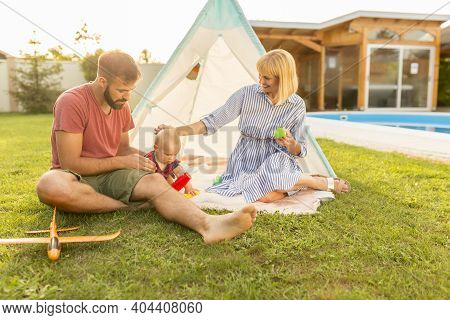 Happy Young Parents Having Fun Camping And Playing With Their Little Baby Boy By The Swimming Pool I