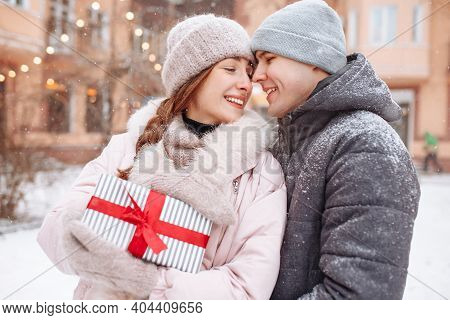 Happy Loving Couple Outside At The Winter Snowy Park Holding A Present With Red Ribbon In Hands. Che