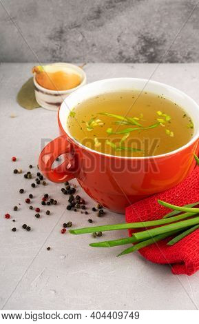 Hot Homemade Vegeterian Vegetable Broth With Amino Acids In Red Bowl With Red Napkin And Green Onion