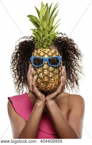 Model with pineapple in hands. African American Girl with Exotic Fruit. Cheerful woman with a smile relaxing on vacation. Image about summer time, smile and rest
