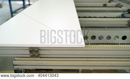 The Machine Makes A Hole In The Wood Panel. A Piece Of Wooden Furniture Rests On The Machine. The Ma