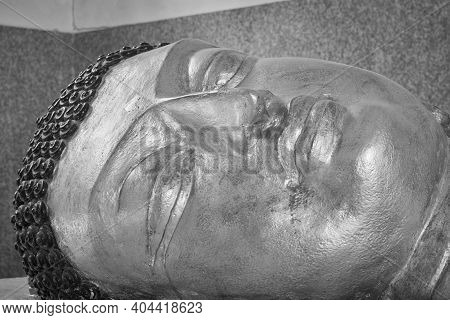 Phayao, Thailand - Dec 6, 2020: Low Angle Black And White Close Up Face Of Gold Buddha Reclining Sta