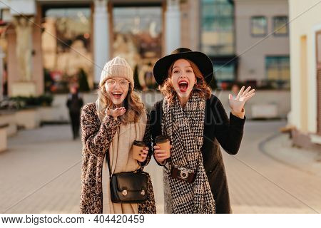 Caucasian Girls Expressing Excitement While Drinking Coffee. Good-humoured Friends Walking Together