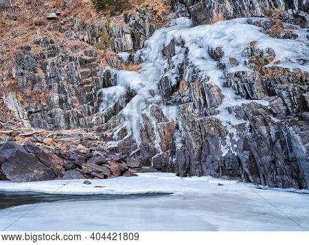 icy cliff on a canyon of mountain river in winter scenery - Poudre River at Little Narrow above Fort Collins, Colorado