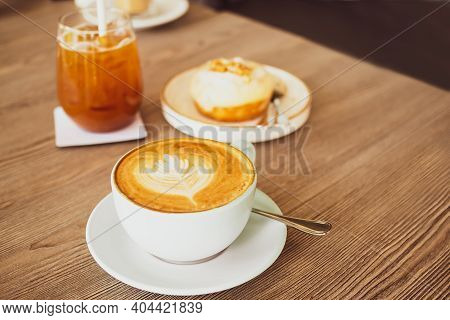 Drink For Winter With Hot Late Coffee In White Cup And Spoon With Blur Image Of Tea And Cake On Wood