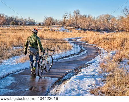 male cyclist is walking his bike through icy spots on a bike trail while commuting along Poudre River in Fort Collins, Colorado in winter scaney