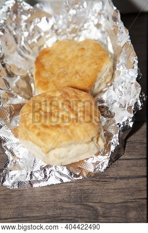 Two Buttermilk Biscuits On Foil On A Wooden Table