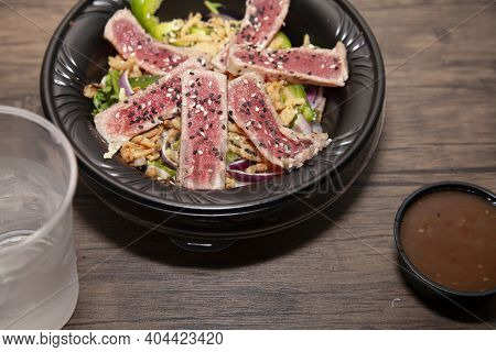Seared Tuna Salad With Lettuce, Sliced Green Bell Pepper, And Red Onion On A Wooden Table Next To A