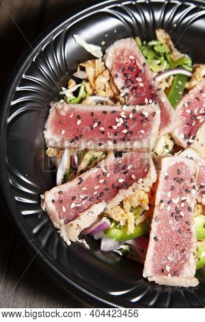 Seared Tuna Salad With Lettuce, Sliced Green Bell Pepper, And Red Onion On A Wooden Table