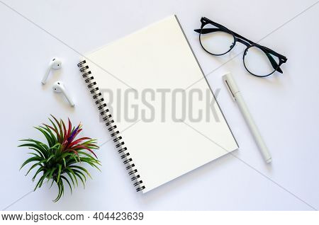 Notebook With Earphone, Spectacles, Pen And Air Plant Tillandsia On White Background.