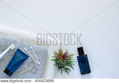 Men Toiletries In Modern Lifestyle On Towels With Air Plant Tillandsia On White Background.