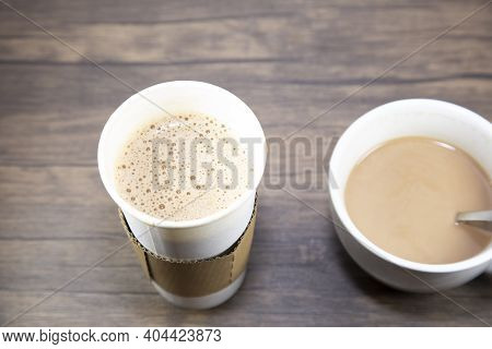 Macchiato In A Carry Out Cup Next To A Latte In A White Cup, Both On A Wooden Table