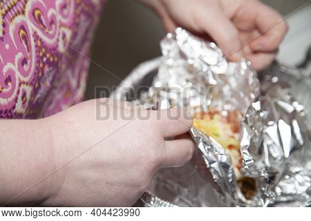 Woman Unwrapping Aluminum Foil From A Pair Of Fresh Tacos