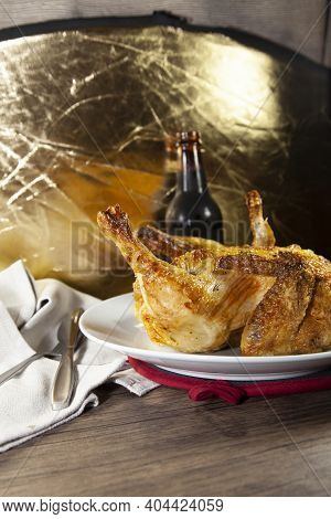 Whole Roasted Chicken On A White Plate And A Bottle Of Beer Next To A Grey Napkin And Silverware