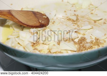 Stir-frying Cut Yellow Onion And Diced Roasted Garlic In A Blue Pan
