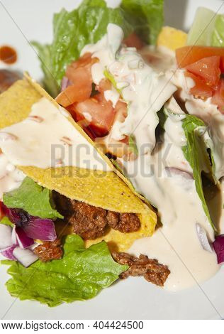 Ground Beef Tacos And Salad Of Romaine Lettuce, Diced Tomato, And Diced Purple Onion On A White Plat