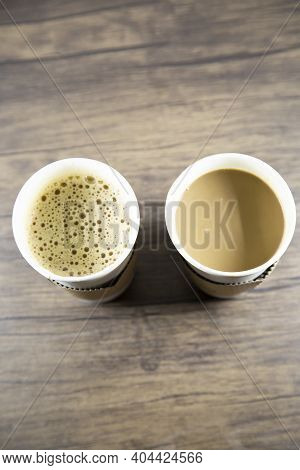 Macchiato And Latte In Carry Out Cups On A Wooden Table