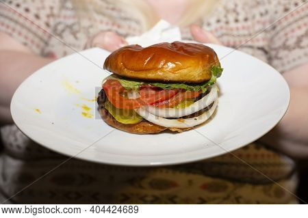 Woman Eating A Well-done Burger With Lettuce, Tomato, White Onion, And Pickles On A White Plate