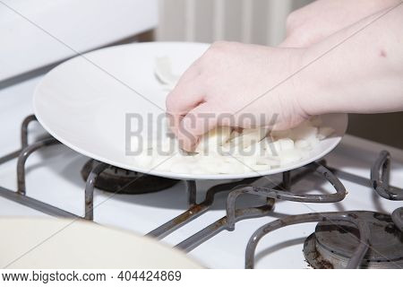 Woman Dicing Yellow Onions On A White Plate