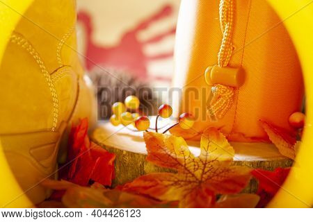 Hunter Orange Pouch On A Wooden Slab Next To Orange And Red Berries And Leaves And A Boot With A Pin