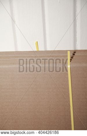 Seven Unused, Flattened Cardboard Boxes In An Open Package With Cut Yellow Bounding