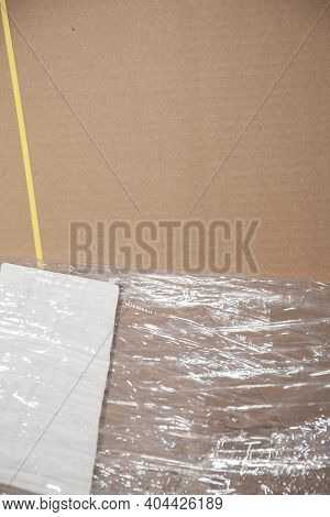 Unused, Flattened Cardboard Boxes In An Open Plastic Package With Yellow Bounding