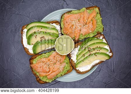Delicious Breakfast. Open Sandwich With Rye Bread, Avocado, Smoked Salmon On Grey Marble Background.