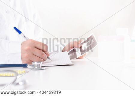 Doctor On Duty Writing Diagnosis After Ultrasound Diagnosis. Doctor In White Uniform With Pen In Han